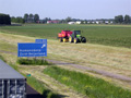 In mei waren wij druk bezig om al het gras in te kuilen en in folie te wikkelen. Zoals u hier ziet: aan de rijksweg A29. Gezien het weer moest alles in korte tijd gebeuren, maar dit was uiteraard geen probleem. (Mei 2005)
